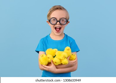 Crazy little boy in funny glasses, shouts and  hugs Easter chicks.