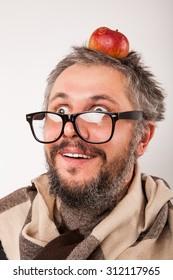 Crazy looking surprised old man with grey beard nerd big glasses with apple on head
