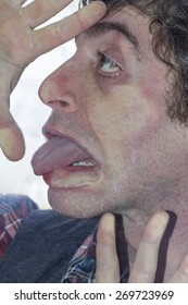 Crazy lunatic man smooshes face against glass surfaces