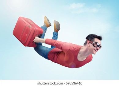 Crazy man in goggles and with red suitcase flies in the sky. Concept of vacation