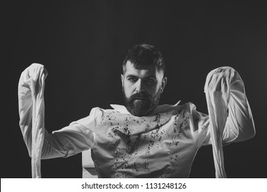 Crazy man. Halloween mummy hipster standing on brown background. Man wrapped in white clothes. Insane, lunatic or mental illness. Captivity and bondage concept. Resurrection and preserving symbol.
