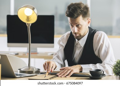 Crazy man with lamp interrogating someone at desk with coffee cup, laptop, supplies and other items