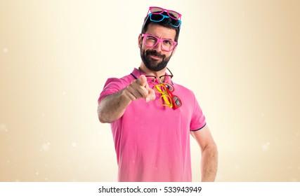 Crazy man with meny glasses on ocher background