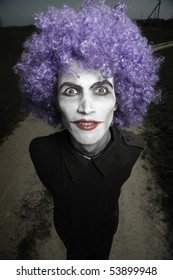 Crazy man outdoors with wig and clown makeup. Artistic darkness and colors added