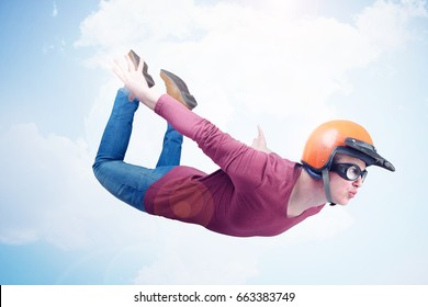 Crazy man in red helmet and goggles is flying in the sky. Jumper concept