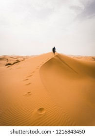 Crazy man running in the desert with the camera in his hand. Fearless hiker he lost in the desert. Morning or evening Sun close to the horizon. Pure nature landscape