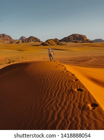 Crazy man running overlooking the red sand desert as seen with a cloudy golden sunset in Wadi Rum, Jordan. Fearless hiker he lost in the desert. Close to the horizon. Pure nature landscape