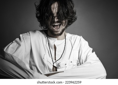 Crazy man with straitjacket screaming trying to break free against gray background with copyspace