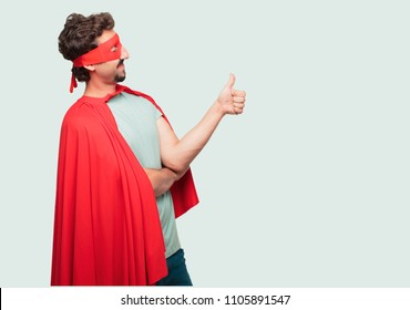 "crazy man as a super hero with a satisfied, proud and happy look with thumbs up, signalining OK with one hand, sending a positive, ""alright' message. Lateral or side view."
