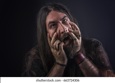 Crazy metalhead long haired man shaking his head and waving his hair, horror, dark and halloween