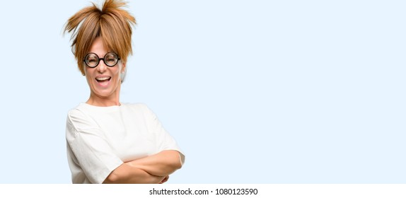 Crazy middle age woman wearing silly glasses with crossed arms confident and happy with a big natural smile laughing isolated blue background
