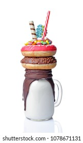 Crazy milk shake with pink and chocolate donuts, color candy and straw in glass jar isolated on white background