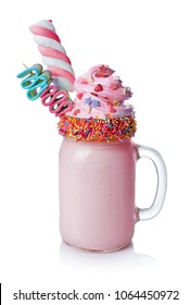Crazy milk shake with pink whipped cream, marshmallow and colored candy in glass jar isolated on white background