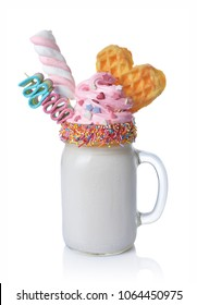 Crazy milk shake with pink whipped cream, marshmallow, waffle and colored candy in glass jar isolated on white background