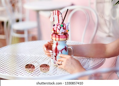 Crazy milkshake in the woman's hands on the white table. Pink and white colors in the background. Sunglasses are laying next to the milkshake on the table. Summertime, outdoors.