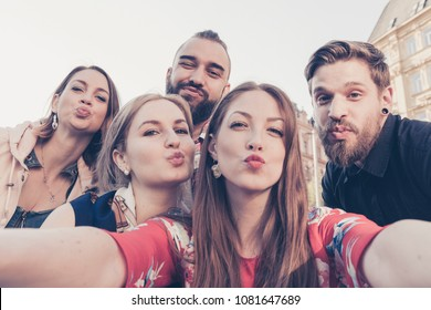 crazy millenials in city environment making duckface expression and  silly faces to share photograph on social media