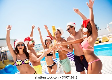 Crazy moves! Non stop seasonal feast at beach resort. Six international hot teens students in diverse swim wear and spectacles have drinks near pool, sunshine, x mas noel mode