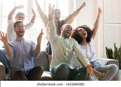 Crazy multiracial people shouting with joy celebrating unbelievable victory of favourite sport team. Diverse friends gathered together in living room eating pop corn watch amusing tv show game concept