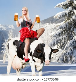 crazy oktoberfest or tiroler creation with a very beautiful woman who is sitting on a cow and serving beer and in the background snow and mountains