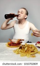 Crazy older man in a-shirt eating lot of junk food.