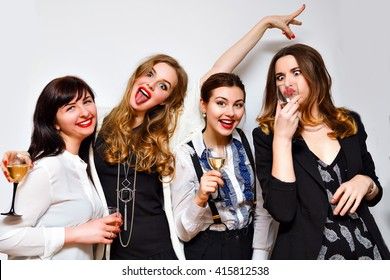 Crazy party image of four pretty woman, having fun at b day celebrating, black and white evening party, glamour clothes hairstyle and make up , funny faces and grimaces. Drinking champagne.