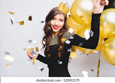 Crazy party time of beautiful women in elegant black dress and yellow crown celebrating new year, birthday, having fun, dancing,drinking alcohol cocktails.Emotion face,red lips, gold balloons
