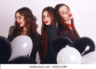 Crazy party time of three beautiful stylish women in elegant casual black outfit celebrating , having fun, dancing. on white background. Best friends wearing black stylish evening dress. Red lips.