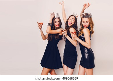 Crazy party time of three  beautiful  stylish  women in elegant casual black outfit  celebrating  new year, birthday , having fun, dancing,drinking alcohol  cocktails .