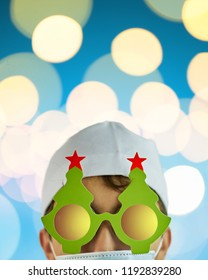 Crazy physician in Christmas tree glasses with red stars and white coat on blue background with bright lights with copy space for text. Vertical crop 4x5. Merry Christmas Doctor