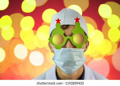 Crazy physician in Christmas tree glasses and white coat and medical mask on red background with bright yellow lights. Copyspace for text. Merry Christmas Doctor