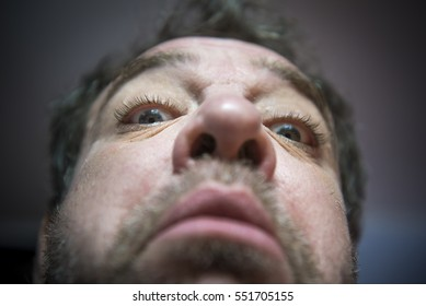 Crazy portrait of a middle-aged man - unshaven, with a red nose. He looks surprised. Angle from the bottom.