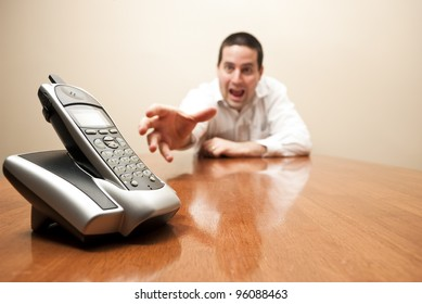 A crazy reaches for a modern cordless phone