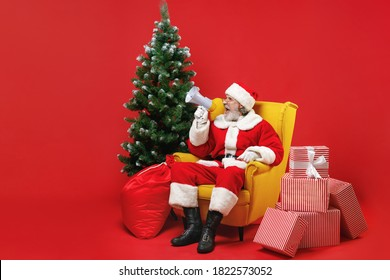 Crazy Santa Claus man in Christmas hat suit glasses sit in armchair with fir tree presents gifts screaming in megaphone isolated on red background. Happy New Year celebration merry holiday concept