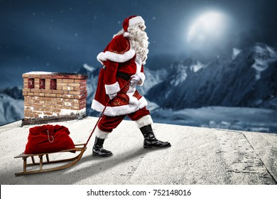 Crazy Santa Claus on a sledge. He's on the roof of the house. Beautiful December night with a big moon in the sky and a view of the mountains full of snow.