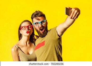 Crazy selfie. Beautiful friends making selfie on yellow background. Studio shot