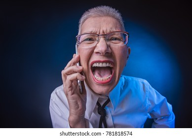 Crazy senior business woman yelling at her cell phone