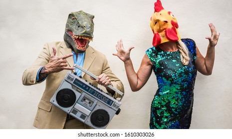 Crazy senior couple dancing at carnival party wearing t-rex and chicken mask - Old trendy people having fun listening music with boombox stereo - Absurd and funny trend concept - Focus on faces - Shutterstock ID 1610303026