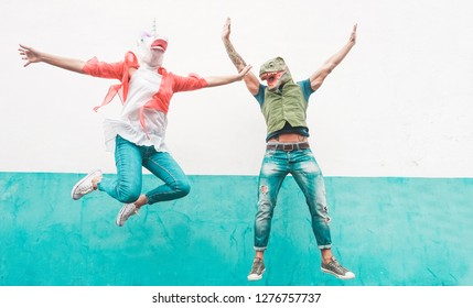 Crazy senior couple jumping wearing t-rex and chicken mask - Old trendy people having fun together- Absurd and funny trend concept - Focus on faces