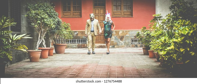 Crazy senior couple walking around city street wearing t-rex and chicken mask - Old trendy people having fun together- Absurd and funny trend concept - Focus on faces - Soft vignette editing