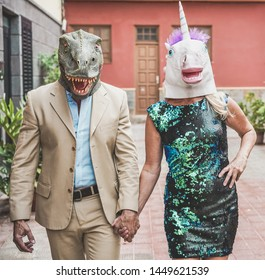 Crazy senior couple walking around city street wearing t-rex and chicken mask - Old trendy people having fun together- Absurd and funny trend concept - Focus on faces