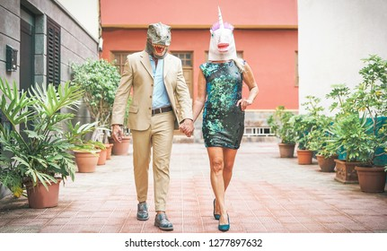 Crazy senior couple wearing dinosaur and unicorn mask - Mature trendy people having fun masked at carnival parade - Absurd, eccentric, surreal, fest and funny masquerade concept