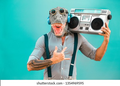 Crazy senior man dancing rock music wearing t-rex mask - Tattoo trendy guy having fun listening music with boombox stereo - Absurd and funny trend concept - Focus on face
