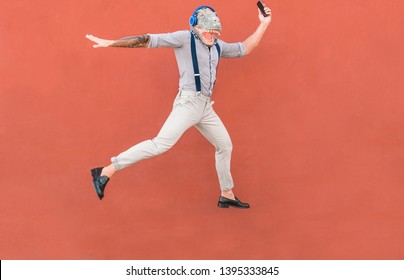 Crazy senior man jumping and dancing rock music wearing t-rex mask - Tattoo trendy guy having fun listening music with headphones - Absurd and funny trend concept - Focus on body