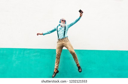 Crazy senior man jumping and listening music outdoor - Happy mature male celebrating and dancing outside - Joyful elderly lifestyle and technology concept - Focus on him