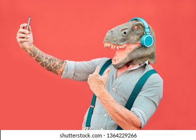 Crazy senior man wearing t-rex mask and taking selfie with mobile smartphone - Hipster older male having fun listening music and dancing outdoor -  Absurd, funny and surreal concepts
