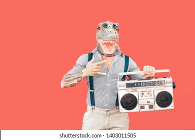 Crazy senior man wearing t-rex mask while listening to music holding vintage boombox stereo outdoor - Fashion masquerade male having fun dancing and celebrating - Absurd and funny people concept