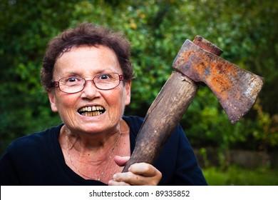 Crazy senior woman holding axe.