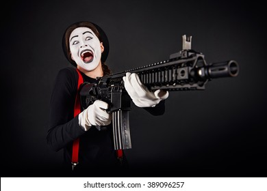 Crazy smiling girl mime with rifle in hands on black background/Crazy smiling mime with gun