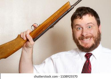 Crazy smiling man holding a gun