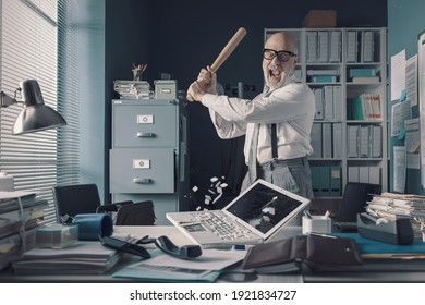 Crazy stressed businessman destroying his desk and laptop with a baseball bat, job burnout concept